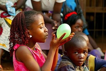Girl holding balloon, Cameroon, Africa