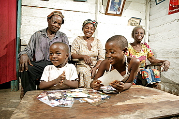 Grandparents and their grandchildren, AIDS orphans, looking at photographs, Cameroon, Africa