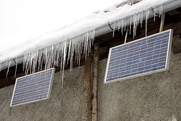 Icicles hanging from raindrainage with solar panels on alpine cottage, Wagner Alm Deutschland