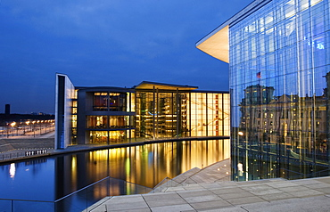 German Bundestag building reflected in the facade of the Marie Elisabeth Lueders House and Paul Loebe House on the opposite side of the Spree River in the evening, Berlin, Germany