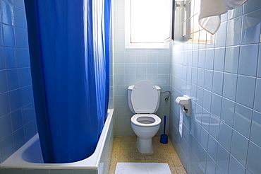 Bath, shower curtain and toilet in a bathroom