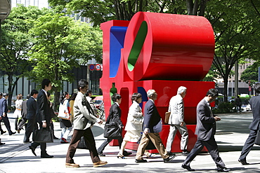 People on their way to work walking by Love-sculpture by American artist Robert Indiana, Shinjuku district, Tokyo, Japan, Asia