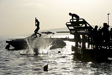 Diving from a dock at Kovacine Campground, with its concrete beach, swimming, and boat docks, Cres Island, Croatia, Europe