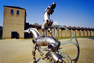 Modern metal plastic horse and rider in front of the reconstructed roman city wall, Xanten Archaeological Park, Lower Rhine, North Rhine-Westphalia, Germany, Europe
