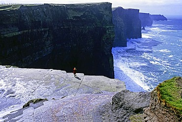 Tourist taking a photo while standing on the Cliffs of Moher, looking south, County Clare, Ireland, Europe
