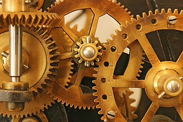 Gear wheels made of golden brass in the clockwork of a historic turret clock
