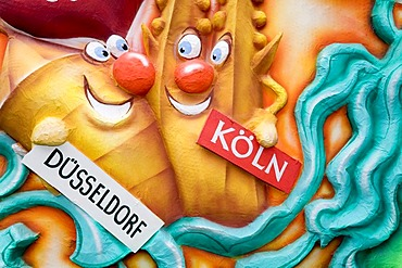 Two cartoon figures symbolize the rivalry between the NRW capital city duesseldorf and the city cologne, caricature made of paper mache , monday before lent parade, Duesseldorf, NRW, Germany
