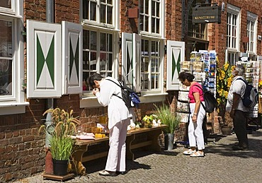 Tourists looking at the special offers in front of a souvenir shop in the dutch quarter of Potsdam, Brandenburg, Germany, Europe
