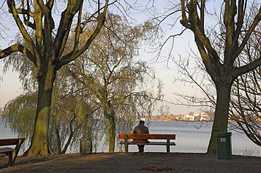 Man sitting on a bench at lake Alster in Hamburg Germany