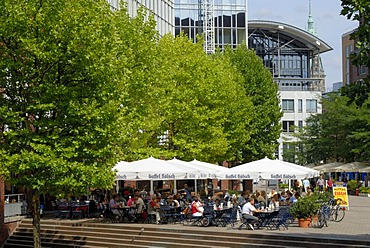 Visitors sitting in front of a sidewalk cafe at the Museumsinsel in the city center of Hamburg, Germany