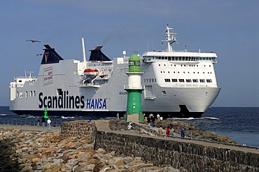 A big ferry ship by Scandlines shipping company passes a lighthouse at the port entrance of Warnemuende, Mecklenburg-Vorpommern, Germany