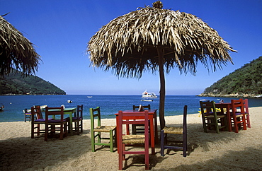 Bay and beach with wooden tables and chairs beneath thatched umbrellas, Bahia de Banderas, Playa Yelapa near Puerto Vallarta, Jalisco, Mexico