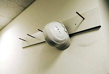 White hard hat on coat hook in front of white wall