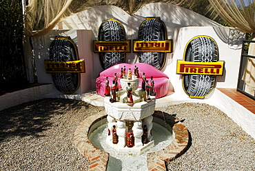 Lip sofa, Pirelli advertising banner and liquor bottle fountain in the garden at the former home of surrealist painter Salvador Dali and his wife Gala in Port Lligat, Province Girona, Spain