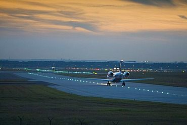 An aeroplane rolls in the evening light to the runway, airport of Frankfurt, Hessen, Germany.
