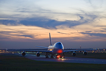 A Boeing 747 is dragged in the evening about the landing field.