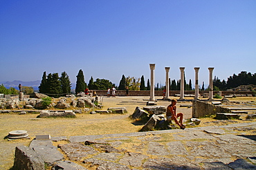 Tourist sitting in front of the ruins at Asklepieion (healing temple), Kos, Dodekanes, Greece, Europe