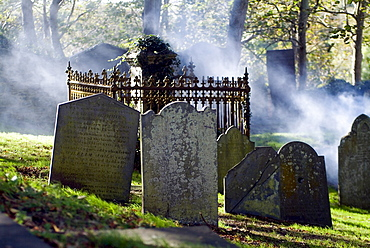 Mist formed over gravestones at a cemetery in St. Davids, Wales, Great Britain, Europe
