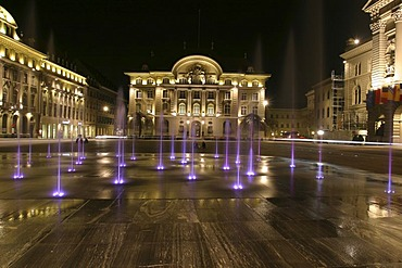 """The 26 water fountains, symbolizing the 26 federal cantons, on the main square in front of the Swiss state house, the """"Bundeshaus"""" in Bern. The square is laid out with granite from Vals in the canton grisons, Switzerland."""