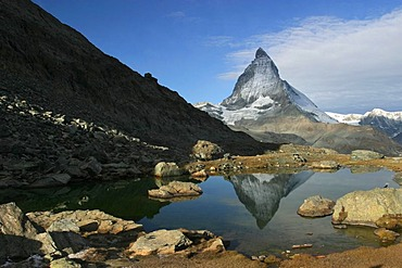 The Matterhorn mountain is reflected in the Riffelsee lake at Gornergrat. Zermatt, Wallis (Switzerland). It is a peak of African crystalline rock, piled up during the continental collision of the African with the European plate that caused the orogeny of
