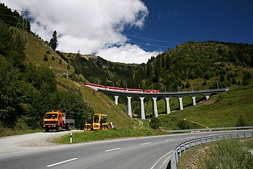 Construction work for Porta Alpina, the underground train stop in the Gotthard base tunnel, with driving work truck and a red train of the Matterhorn-Gotthard-Bahn (background), Sedrun, Grisons, Switzerland