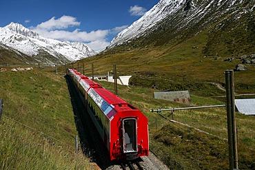 Cog railway section of the Matterhorn-Gotthardbahn (MGB) with red train coaches at the Oberalppass, Grisons/Uri, Switzerland