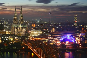 Illuminated city center with Hohenzollern bridge, central train station and cathedral, Cologne, NRW, Germany