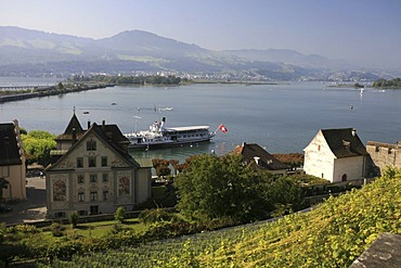 View from the castle hill to Lake Zurich and the isles of Ufenau and Luetzelau and tourist ships in the harbor of Rapperswil, St. Gall, Switzerland
