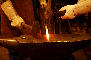 Glowing iron rod being hammered into shape against an anvil by two smiths wearing long white leather gloves, Industrial Museum, Lauf an der Pegnitz, Bavaria, Germany, Europe