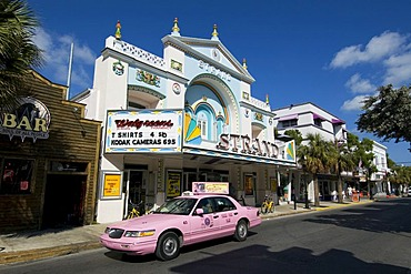 Pink cab driving past Strand's Department Store in Key West, Florida, USA