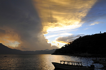 Sunset, back light, dramatic clouds, boat, Lake Atitlan, Guatemala, Central America
