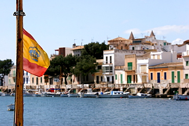 Spanish flag with crown in the harbour of Porto Colom, Majorca, Spain, Europe