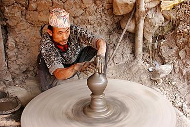 Potter at work on an outdoor pottery square in Bhaktapur, Nepal - 832-343656