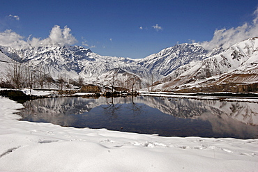 Snow-covered mountains reflected in a lake near the remote mountain village Jharkot along the popular Jomsom Trail, Jharkot, Nepal, Asia