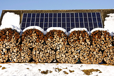 Solar panels and stacked firewood in wintertime near Schluchsee (Schluch Lake), Black Forest, Baden-Wuerttemberg, Germany, Europe