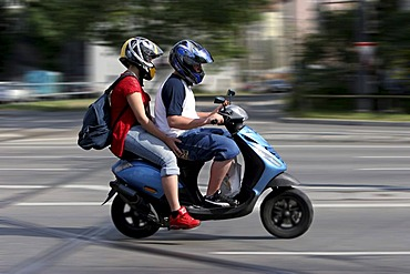 Couple on driving motor scooter, Munich, Upper Bavaria, Bavaria, Germany