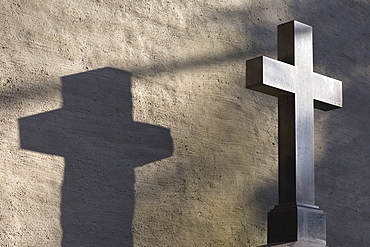 Cross throwing a shadow at a grave, Alter Suedfriedhof, old cemetery in Munich, Bavaria, Germany