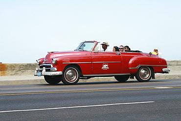 Car driving on Malecon Road alongside Estrecho de la Florida bay in Havana, Cuba, Caribbean, Americas