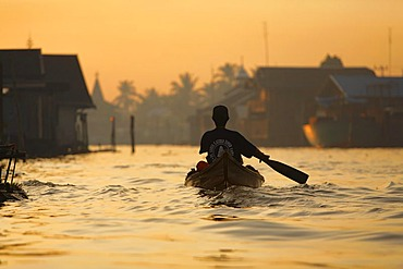 Man in boat on distributary of Sungai Barito near Banjarmasin, South-Kalimantan, Borneo, Indonesia