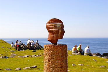 Group of hikers taking a break behind head, art piece designed by artist Markus Raetz, Lofoten, Norway
