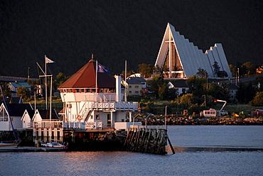 Harbour in front of modern triangular Christian church, Ishavskatedralen (Arctic Cathedral aka Tromsdalen Church), Tromsoe, Norway