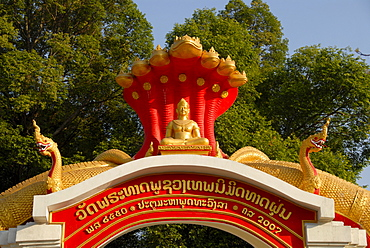 Entrance gate to the buddhist monastery Wat That Fune, decorated with golden snakes, Nagas, Vientiane, Laos, Asia