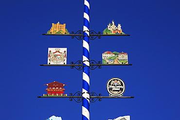 Maypole with signs of Neuschwanstein and Hohenschwangau, Schwangau near Fuessen, Bavaria, Germany
