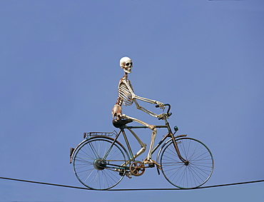 Skeleton riding a bike on a wire cable