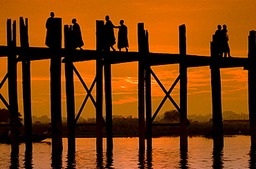 Buddhist monks walking over an old teak bridge at sunset, Mandalay, Myanmar (Burma), Southeast Asia