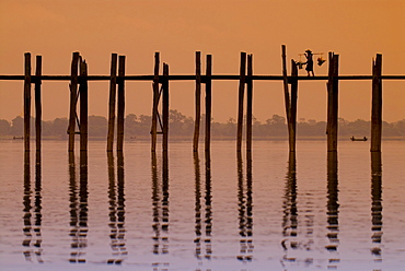 Man carrying a load crossing the U Bein Bridge at sunset, old wooden teak bridge, Mandalay, Myanmar, Southeast Asia