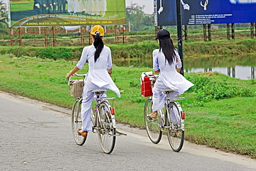 Students in the traditional ao dai dress on the way to school Vietnam
