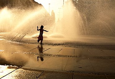Child playing in the Stachus Fountain, Munich, Bavaria, Germany, Europe