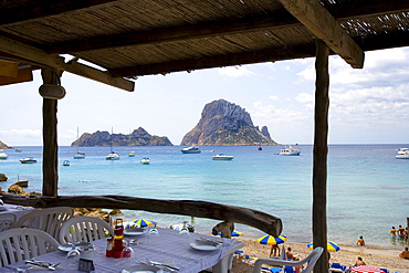 Beach restaurant in the bay of Cala d¥Hort, view of rock island Es Vedra, Ibiza, Balearic Islands, Spain, Europe