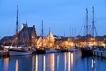 Old sailing boats in the old harbour of Wismar, at back the Nikolaikirche Church and the Wassertor Gate lit up at dusk, Wismar, Baltic Sea, Mecklenburg-Western Pomerania, Germany, Europe